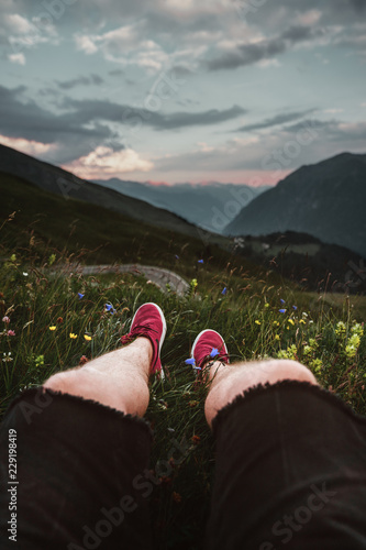 Mann sitzt auf eine Wiese bei Sonnenuntergang an der Grossglockner Höhenstrasse und bilckt auf die Alpen