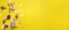 Christmas And New Year Concept. Greeting Banner With Copyspace. Shiny Silver Deer, Stars, Fir-tree, Garland, Bokeh On Yellow Background. Top View, Flat Lay