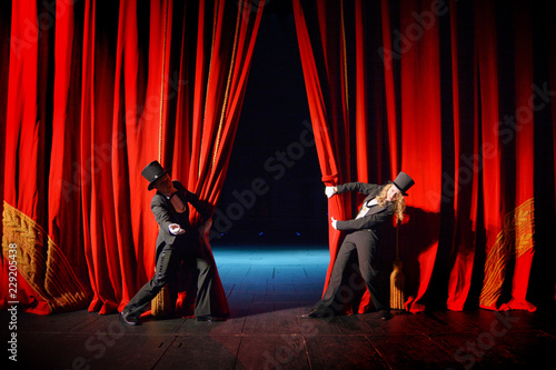 Fototapeta Actors in tuxedos and hats look behind the theater curtain obraz