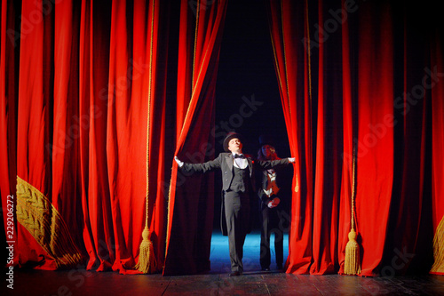 Fototapeta  Actor and actress in tuxedos open theater curtain