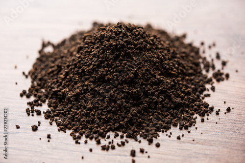 Photo Black Tea Powder or dry dust with or without green leaf and served hot chai in a