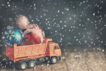 A Large Dump Truck Carries Christmas Balls During Blizzards And Snowfall.