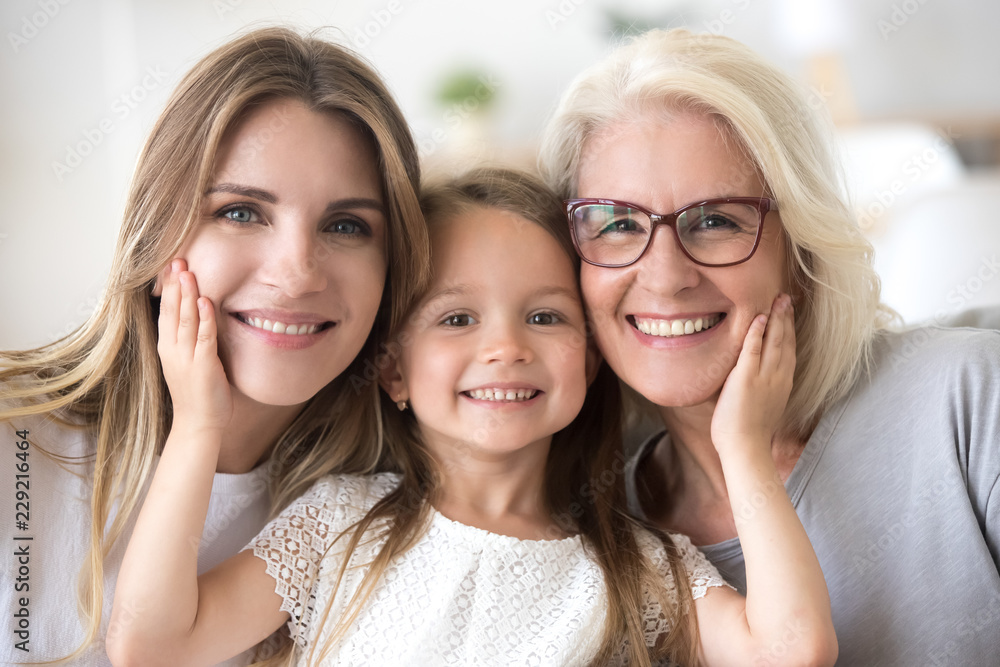 Fototapeta Portrait of three generations of women look at camera posing for family picture, cute little girl hug mom and granny enjoy time at home, smiling mother, daughter and grandmother spend weekend together