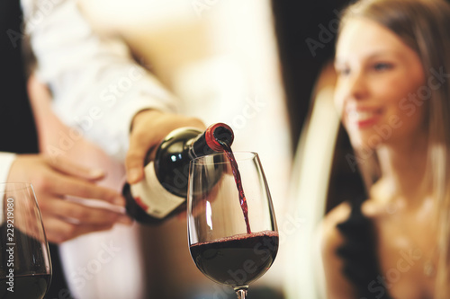 Waiter pouring wine