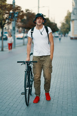 Fototapeta Portrait of young man walking with thoughtfully classic bicycle on city streets