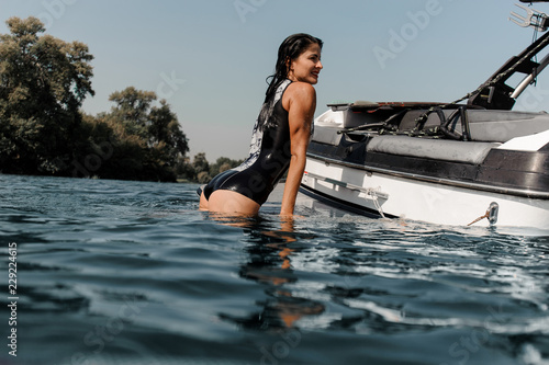 Brunette girl climbing on the motorboat on the lake Tapéta, Fotótapéta
