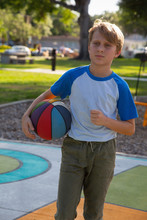 A Boy Playing With A Basketball At The Park.