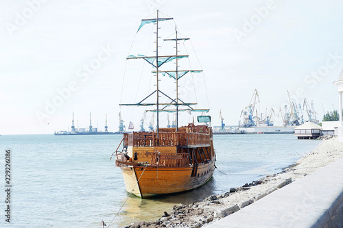 Romantic wooden brown ship with blue sails by the sea