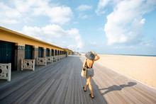 Woman Walking On The Beach With Locker Rooms In Deauville, Famous French Resort In Normandy. Wide Angle View