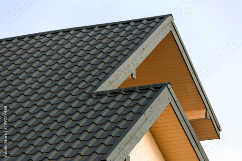 Stampa su Tela Close-up detail of new modern house top with shingled green roof on clear blue sky background