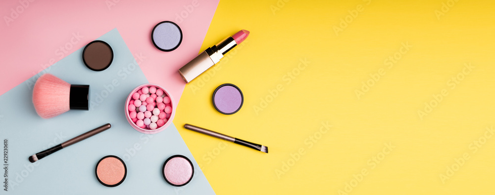 Fototapeta Makeup products and decorative cosmetics on color background flat lay. Fashion and beauty blogging concept. Long web format for banner