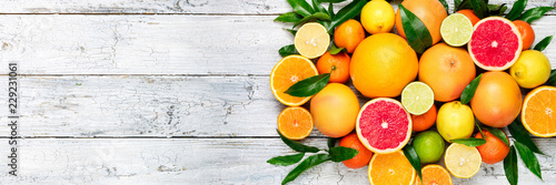 Fresh citrus fruits background. Orange, grapefruit, lemon, lime, tangerine. Mix citrus fruits with leaves. Long web format. Copy space