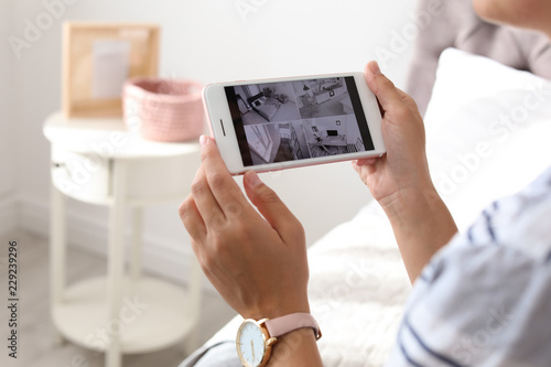 Woman monitoring modern cctv cameras on smartphone indoors, closeup Canvas Print