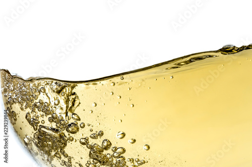 Leinwand Poster Splash white wine in glass with bubbles close-up macro texture isolated on top on white background