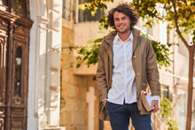 Outdoor Image Of Handsome Young Man With Books Outdoors. College Male Student Carrying Books In College Campus In Autumn Street Background. Smiling Cheerful Guy With Curly Hair Posing With Books.