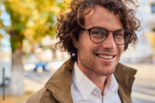 Fototapeta Closeup horizontal portrait of young happy business man with glasses smiling and posing outdoors