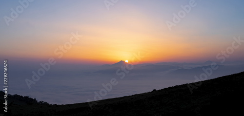 Fog in mountains. White wavy fog at the sunrise. landscape of mountains with the sun in the background