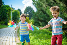 Two Happy Children Playing In Garden With Windmill Pinwheel. Adorable Sibling Brothers Are Best Friends. Cute Kid Boy Smile Spring Or Summer Park. Outdoors Leisure Friendship Family Concept