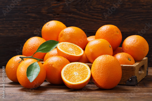 fresh orange fruits in a box on wooden table