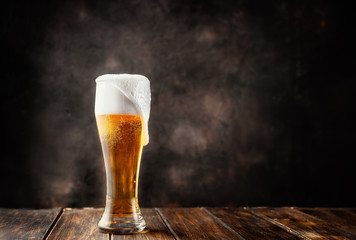 Čaša svježeg i hladnog piva na tamnoj pozadini