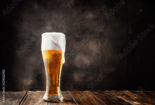 Fotografia  Glass of fresh and cold beer on dark background