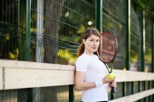 Fotografiet  Young female tennis player with tennis ball and racket preparing to serve