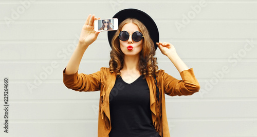 Photo Fashion woman taking picture selfie by smartphone in black round hat, sunglasses