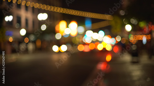Leinwand Poster Blurry background plate of city traffic at night with bokeh headlights passing