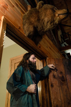 Bearded Man Poses Under A Bear Head In A Robe In A Cabin In Upstate New York