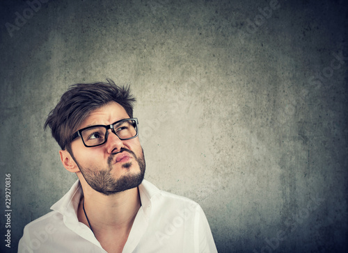 Doubtful man making grimace while thinking