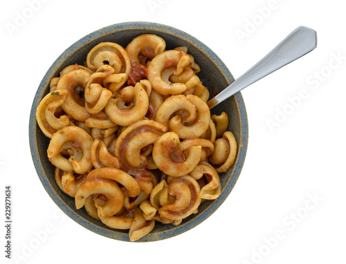 Fotografie, Obraz  Overhead view of cold pasta with tomato chunks and seasonings with olive oil in an old stoneware bowl with a fork in the food isolated on a white background