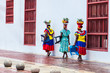 Leinwanddruck Bild - Traditional fruit street vendors in Cartagena de Indias called Palenqueras walking in front of the building of the town hall of Cartagena
