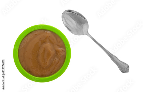Fotografie, Obraz  Top view of a serving of mocha instant pudding in a small green bowl with a spoon to the side isolated on a white background