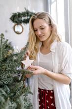 Woman Putting Star On Fir Branch