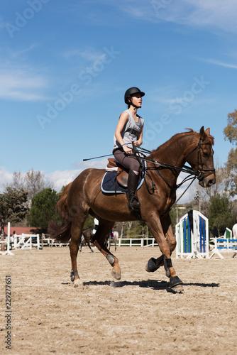 Confident woman riding horse on hippodrome