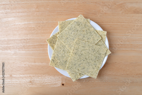 Top view of several slices of garlic cheddar cheese on a white plate atop a wood table.