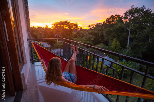Fotografie, Obraz  Woman relaxes in the hammock set on a balcony and enjoys sunset and tropical gar