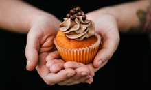 Two Hands Holding A Cupcake