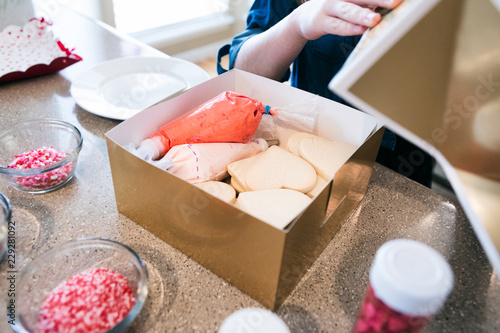 Deurstickers Koekjes Valentine: Girl Opens Holiday Cookie Kit