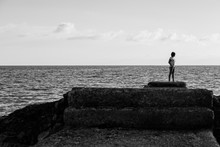 Woman On A Rock Dock At Sunset