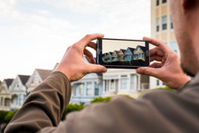 Man Uses A Smartphone To Photo...
