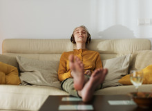 Relaxing Woman Listening To Music On Sofa