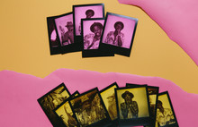 Two Rows Of Duochrome Polaroid Instant Prints In Yellow And Black And Pink And Black Over Ripped Yellow And Pink Paper