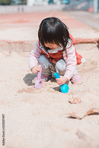 Asian little girl playing in sand