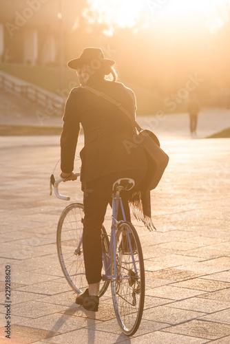 Deurstickers Fiets Anonymous man riding city bike in the golden hour