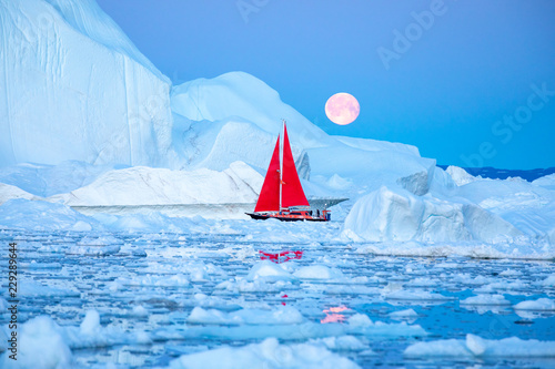Fotografia Little red sailboat cruising among floating icebergs in Disko Bay glacier during midnight sun season of polar summer