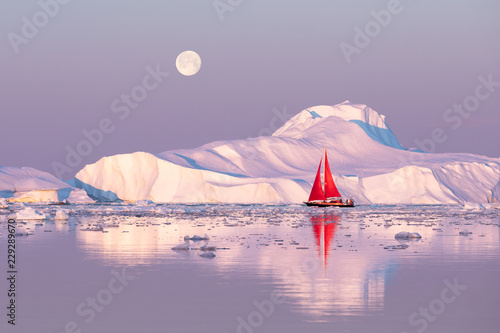 Fényképezés  Little red sailboat cruising among floating icebergs in Disko Bay glacier during midnight sun season of polar summer