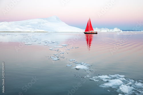 Little red sailboat cruising among floating icebergs in Disko Bay glacier during midnight sun season of polar summer Canvas Print
