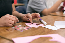 Classroom: Girl Adds Heart Stickers To Cut Out Valentine