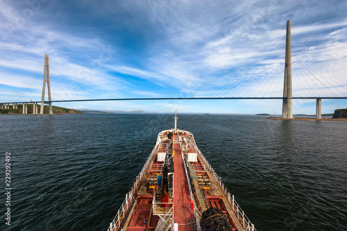 Tanker is moving under a large cable-stayed bridge.